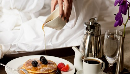 Breakfast in bed with our famous three stacked pancakes with thick organic maple syrup.