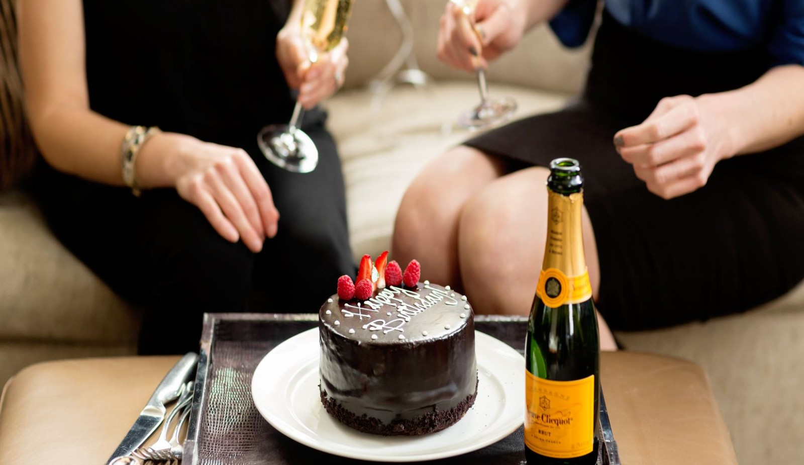 A chocolate Happy Birthday Cake alongside a bottle of champagne. This is part of our Birth Celebration Package on our website.