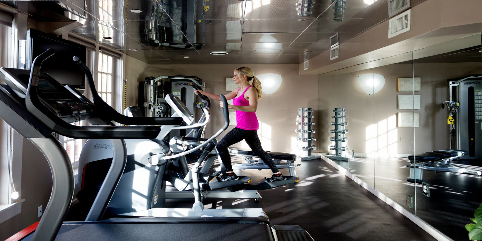 Photograph if a beautiful woman working out on our elliptical machine in our 24/7 fitness center.