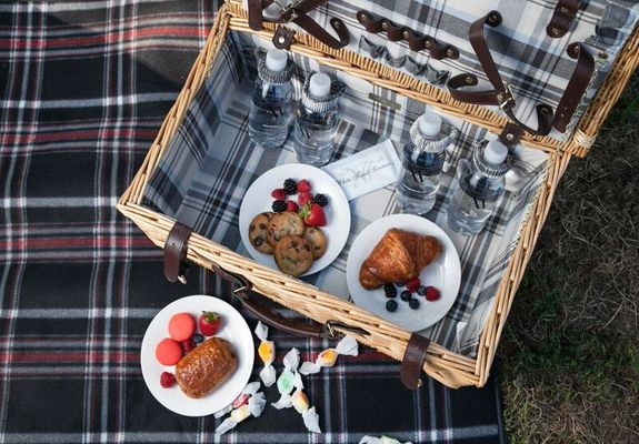 Open picnic basket with four bottle waters, chocolate chip cookies and a break croissant showcased in the inside of the basket.