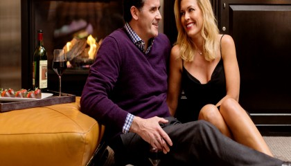 A romantic photograph of a man and a women sitting on the floor next to the fireplace in the Beacon Hill Studio room. The couple is enjoying red wine and chocolate covered strawberries.
