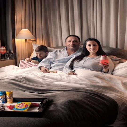 Family of four in bed enjoying our movie night themed in-room dining packages.