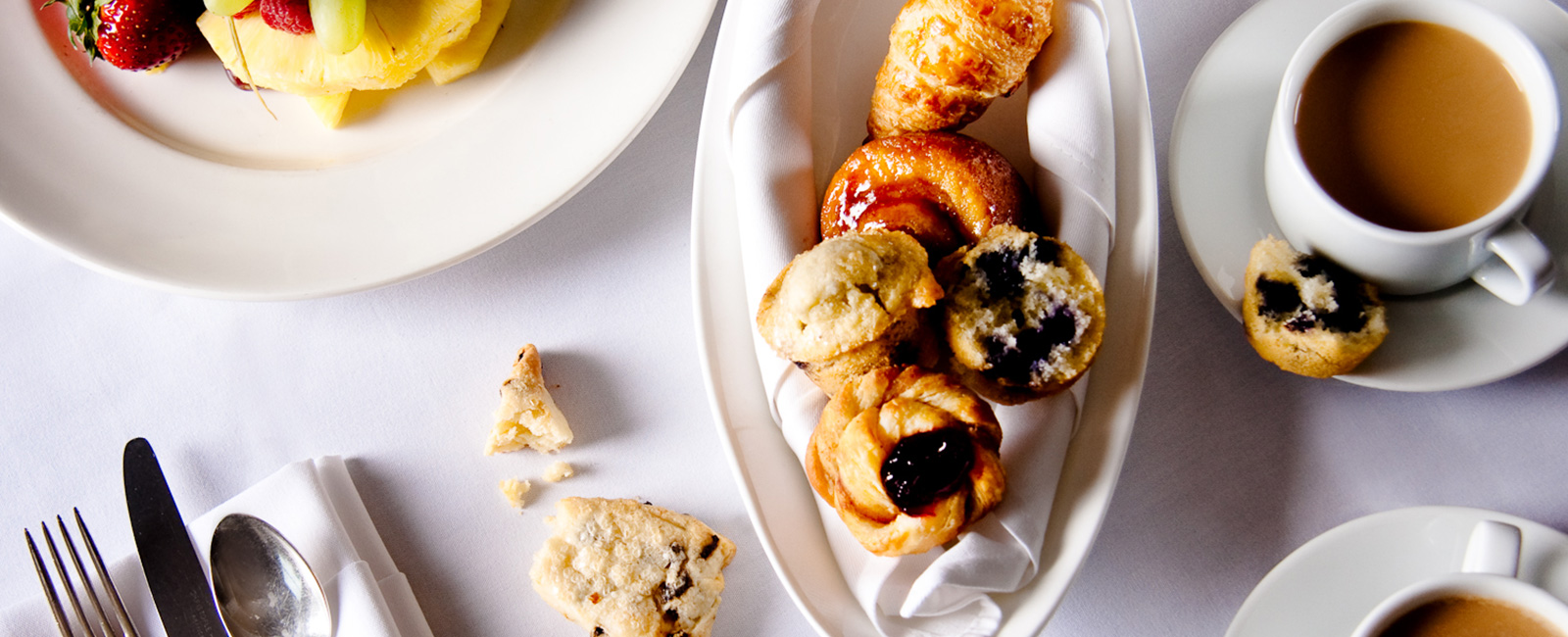 Photograph of some of breakfast menu options to include; muffins, pastries, coffee, and fresh fruit.