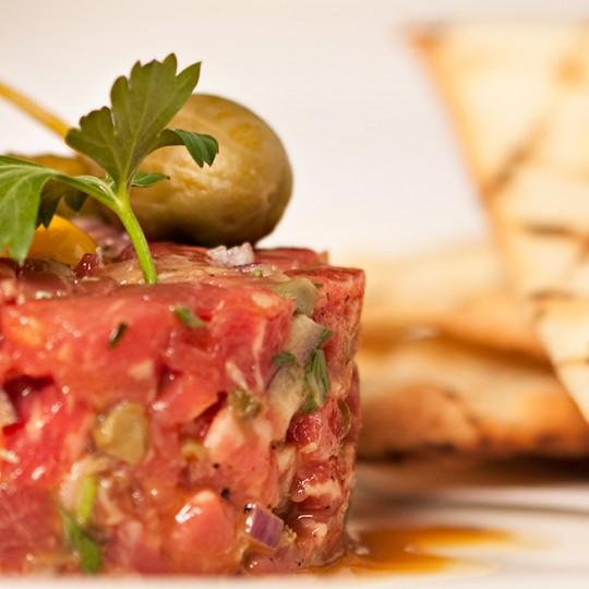 steak tartar with a green pickle and a green olive on top. Serviced with toasted pita bread