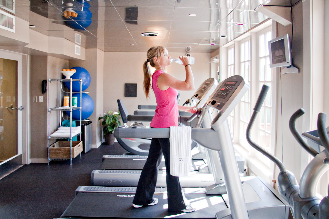 Photograph if a beautiful woman working out on our treadmil machine in our 24/7 fitness center.