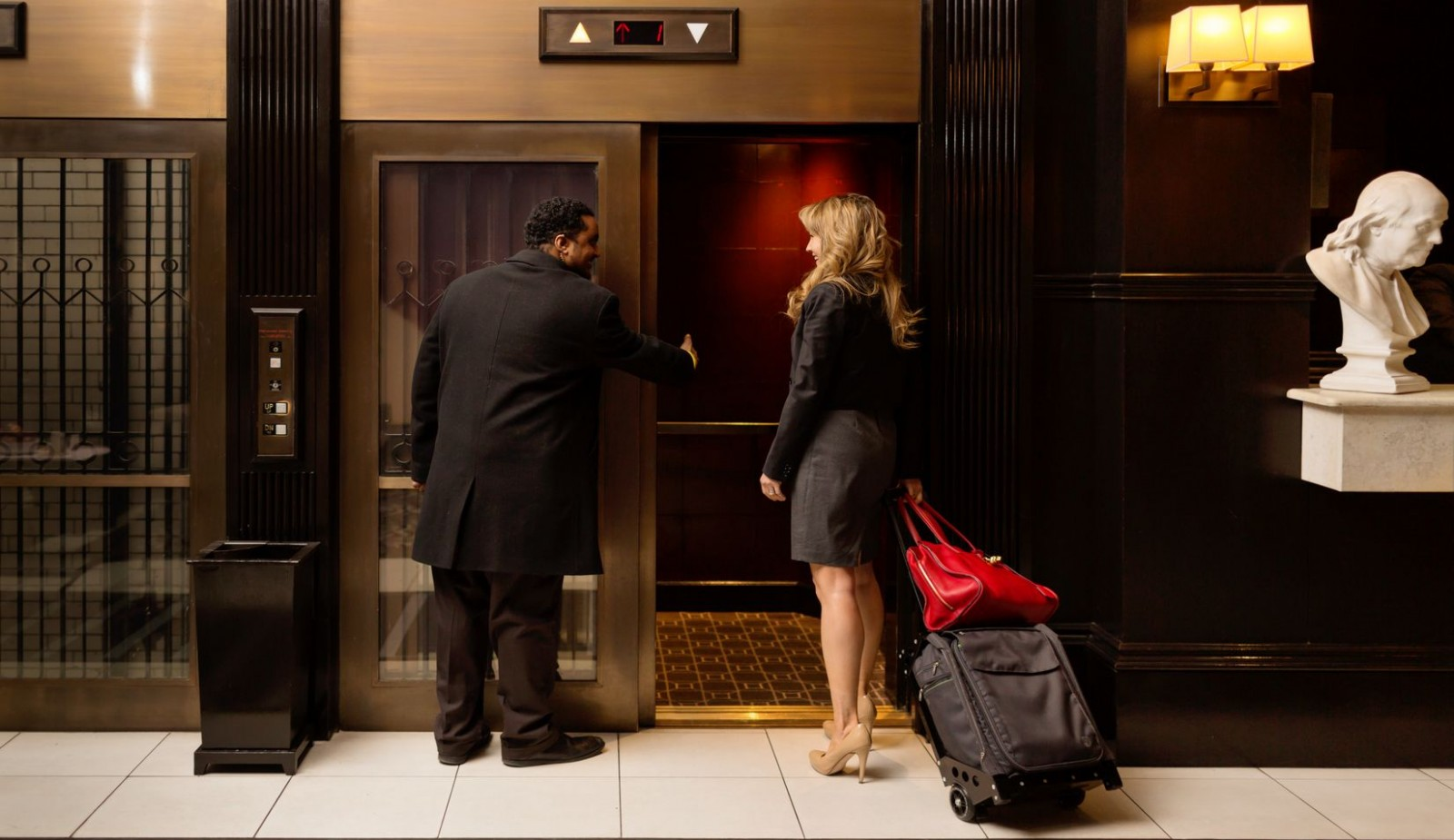 One of our bellman assistance a young lady into our 1903 historic elevators.