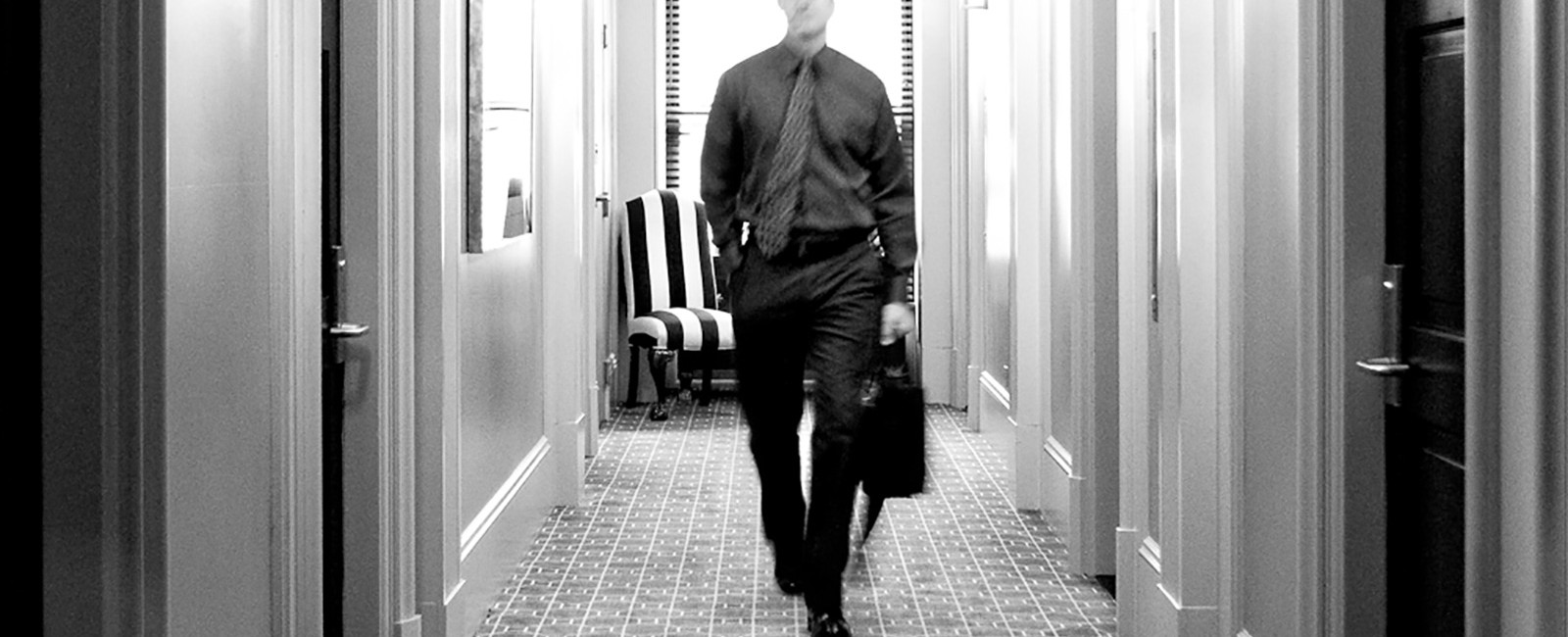 black and white photograph of a guest walking towards the elevators from his room.