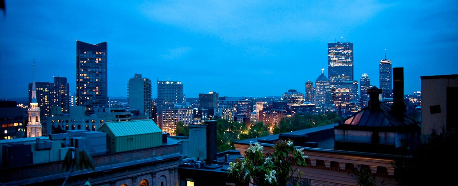 Fifteen Beacon's view from our roof deck overlooking Boston's building after dark.