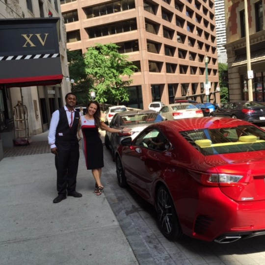 Doorman and our general manager next to a red Lexus outside the front of the hotel.
