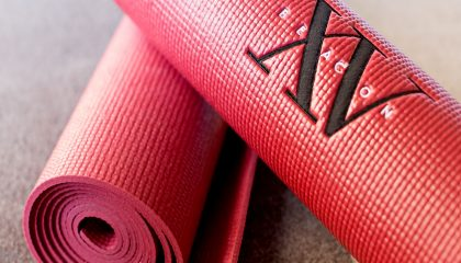 Red yoga mats with the Fifteen Beacon logo in the middle of the mat.