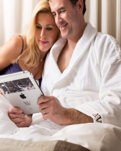 Man and Women photo in bed with white robe on the man. Both are looking at the hotel's Ipad.