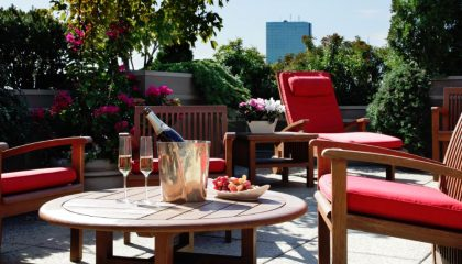 Roof deck table with red cushions featuring fresh fruit and a bottle of champagne