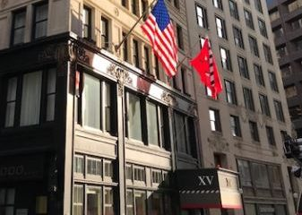 Exterior of the hotel from the street level along with the Fifteen Beacon Logo flag and American Flag