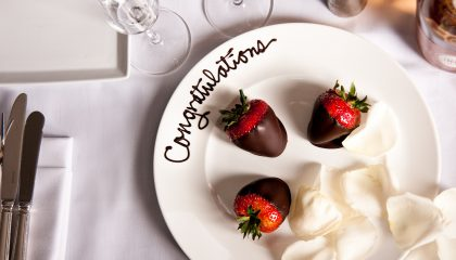 Three chocolate covered strawberries with white rose petals on a perfectly decorated white plate. Also to include a written congratulations in chocolate on the top of the plate.
