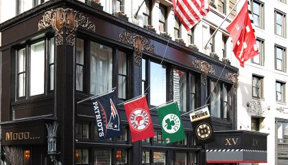 Exterior of XV Beacon Hotel with flags to represent Boston Sports Teams