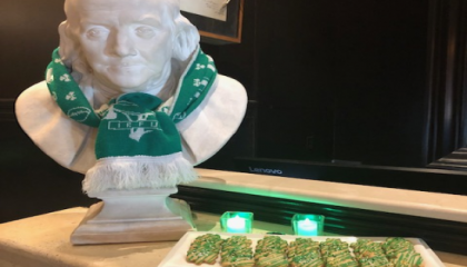 st patricks day photo of hotel with green scarf on Ben Franklin statue