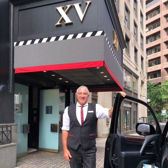 male hotel employee standing outside of the XV Beacon Hotel