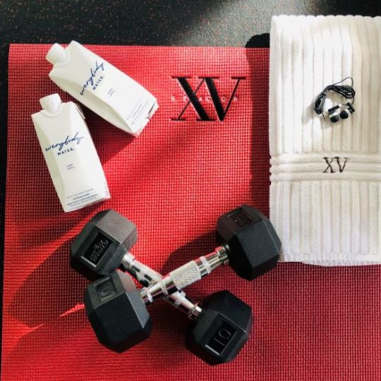 Photo of our XV Beacon Yoga mat, 10 pound free weights, XV Beacon hand towel with headphones on top of the towel along side our new water from everybody water
