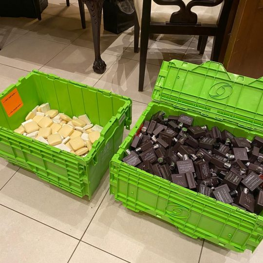 two green bins full of unused soap that the hotel donates