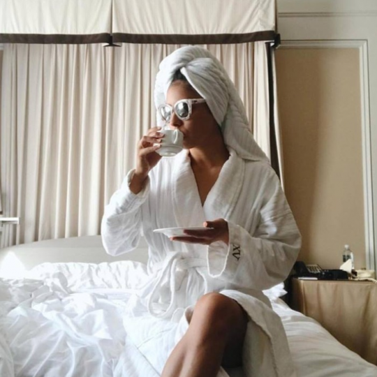 woman on XV Beacon Bed with our custom Frette Robes