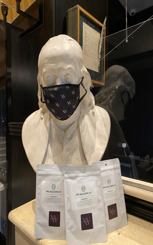 Photo of the Ben Franklin statue in our lobby with a COVID-19 mask on
