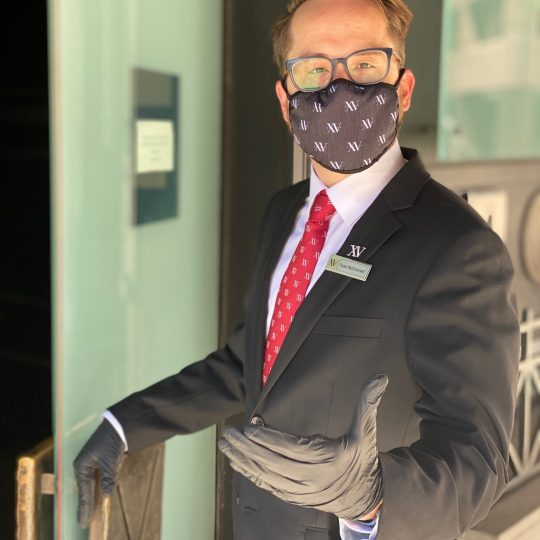 Employee welcoming you to XV beacon wearing a face mask