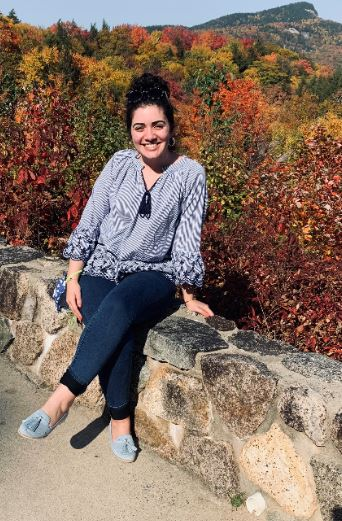 photo of our Front office supervisor, Myriam outside with fall foliage as the backdrop.