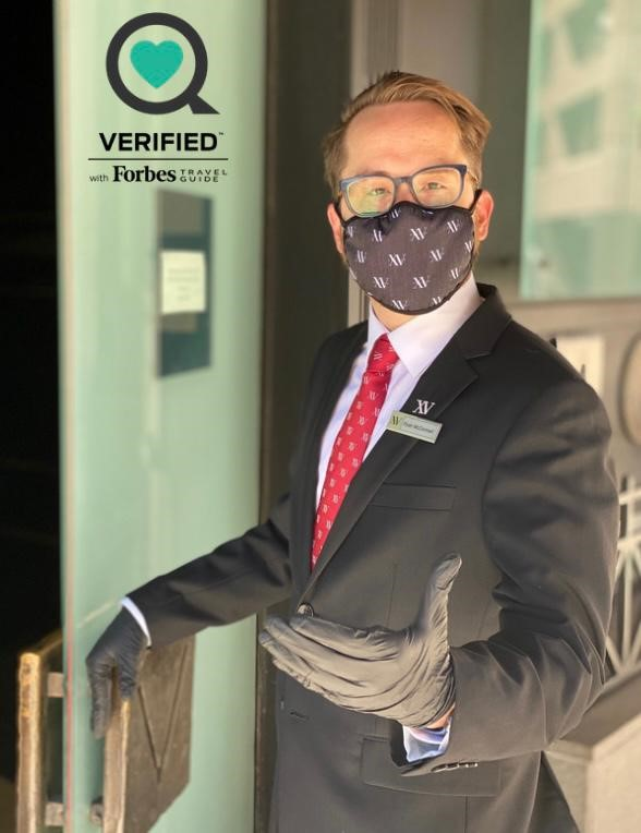 Front Doorman with Mask On Welcoming Guest to the Hotel. Forbes Verified Logo on the Top Left Corner