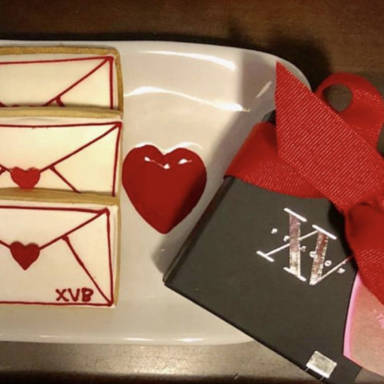 Photo of XV Beacon's Valentines Day Cookies with a small box of chocolates with a red ribbon