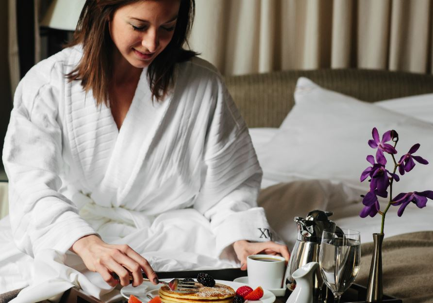 Woman Guest in XV Beacon's signature robe enjoying her in-room dining pancake breakfast